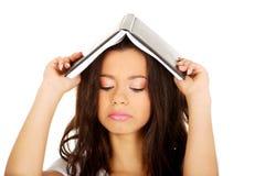 Mujer del estudiante con un libro en la cabeza Fotos de archivo libres de regalías