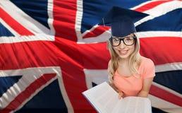 Mujer del estudiante en birrete sobre bandera inglesa Fotografía de archivo