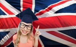 Mujer del estudiante en birrete sobre bandera inglesa Foto de archivo libre de regalías