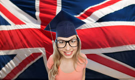 Mujer del estudiante en birrete sobre bandera inglesa Imágenes de archivo libres de regalías
