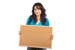 Mujer del estudiante que sostiene el corkboard vacío Foto de archivo libre de regalías