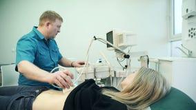 Mujer del examen del ultrasonido de la diagnosis del estómago dentro almacen de video