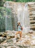Mujer del explorador que camina delante de la cascada imagenes de archivo