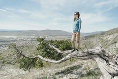 Mujer del explorador que se coloca en árbol Imagenes de archivo
