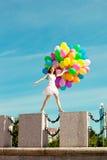 Mujer del feliz cumpleaños contra el cielo con los balones de aire arco iris-coloreados  fotografía de archivo libre de regalías