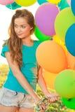 Mujer del feliz cumpleaños contra el cielo con vagos arco iris-coloreados del aire imagen de archivo libre de regalías