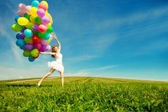 Mujer del feliz cumpleaños contra el cielo con vagos arco iris-coloreados del aire fotografía de archivo
