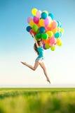 Mujer del feliz cumpleaños contra el cielo con vagos arco iris-coloreados del aire fotos de archivo libres de regalías