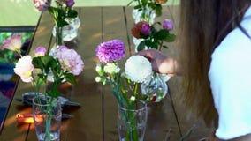 Mujer del florista acabada a arreglar las flores en el vidrio al aire libre que elimina el núcleo casandose la cámara lenta metrajes