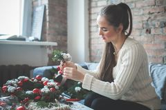 Mujer del florista o del decorador que hace decoraciones de la Navidad fotografía de archivo