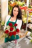 Mujer del florista que arregla el funcionamiento del departamento de las rosas de las flores Imagen de archivo