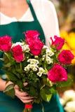 Mujer del florista que lleva a cabo las manos del ramo de las rosas rojas Fotos de archivo