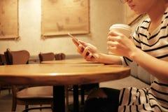 Mujer del fondo de la forma de vida que sostiene el vidrio del café y que usa el móvil Fotografía de archivo
