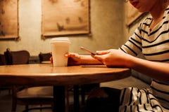 Mujer del fondo de la forma de vida que sostiene el vidrio del café y que usa el móvil Foto de archivo libre de regalías
