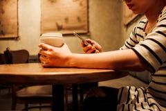 Mujer del fondo de la forma de vida que sostiene el vidrio del café y que usa el móvil Imagenes de archivo