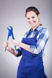 Mujer del fontanero con la llave Imagen de archivo libre de regalías