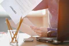 Mujer del Freelancer que lee un contrato que se sienta en la tabla Fotos de archivo