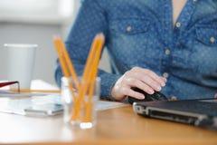 Mujer del Freelancer que trabaja en el ordenador mientras que se sienta en la tabla Imagen de archivo