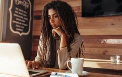Mujer del Freelancer que trabaja en el ordenador portátil en un café fotos de archivo