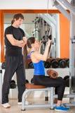 Mujer del gimnasio con el hombre personal del instructor fotografía de archivo libre de regalías