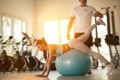 Mujer del gimnasio con el hombre personal del instructor fotografía de archivo