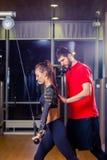 Mujer del gimnasio que ejercita con su instructor personal foto de archivo libre de regalías