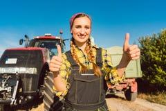 Mujer del granjero delante de la maquinaria agrícola que da los pulgares-para arriba fotos de archivo