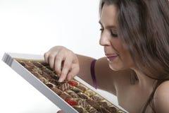 Mujer del gusto por lo dulce con las almendras garapiñadas Imagenes de archivo