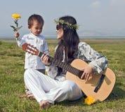 Mujer del Hippie que toca la guitarra con el hijo Imagen de archivo libre de regalías