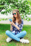Mujer del hippie que usa el smartphone que se sienta en hierba en jardín floreciente Fotografía de archivo