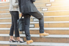 Mujer del hombre de negocios y de negocios que camina encima de las escaleras con los bolsos Foto de archivo libre de regalías