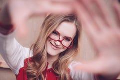 Mujer del inconformista con las lentes rojas que hacen gesto que enmarca del foco Imagen de archivo