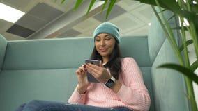 Mujer del inconformista de la raza mixta de Millenial en café que charla con los amigos que usan el teléfono móvil almacen de metraje de vídeo