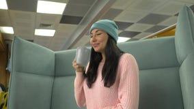Mujer del inconformista de la raza mixta que se sienta en el café, café de consumición y usando smartphone almacen de metraje de vídeo