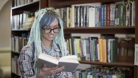 Mujer del inconformista en vidrios con los dreadlocks que sonríe y libro de lectura en biblioteca almacen de video