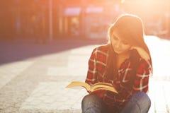 Mujer del inconformista que goza de un buen libro que se sienta en la igualación soleada al aire libre Foto de archivo libre de regalías