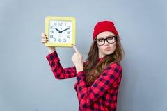 Mujer del inconformista que señala el finger en el reloj de pared Fotografía de archivo