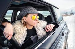 Mujer del inconformista que se sienta en un pequeño coche Foto de archivo