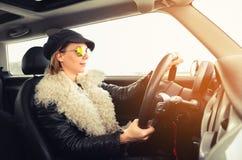 Mujer del inconformista que se sienta en un pequeño coche Imagen de archivo libre de regalías