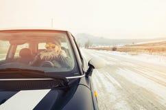 Mujer del inconformista que se sienta en un pequeño coche Fotos de archivo libres de regalías