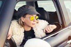 Mujer del inconformista que se sienta en un pequeño coche Foto de archivo libre de regalías