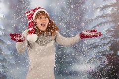 Mujer del invierno con el sombrero de la Navidad Papá Noel en nieve Foto de archivo libre de regalías