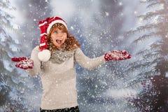Mujer del invierno con el sombrero de la Navidad Papá Noel en nieve Imagen de archivo libre de regalías