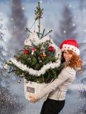 Mujer del invierno con el sombrero de la Navidad Papá Noel y del árbol Imagen de archivo