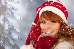 Mujer del invierno con el sombrero de Santa Claus en nieve Imagen de archivo libre de regalías