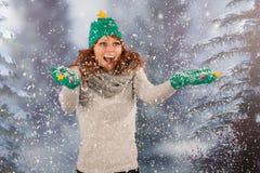 Mujer del invierno con el sombrero del árbol de navidad y de la diversión en la nieve Fotografía de archivo
