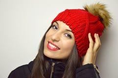 Mujer del invierno de la moda con sonrisa roja del sombrero de las lanas en la cámara en el fondo blanco imagen de archivo libre de regalías