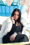 Muchacha del invierno en abrigo de pieles de lujo en el teléfono móvil Fotografía de archivo libre de regalías