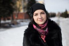 Mujer del invierno en la nieve que mira para arriba en día de invierno frío que nieva Fotografía de archivo