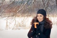 Mujer del invierno que sostiene una taza caliente de la bebida fotografía de archivo libre de regalías